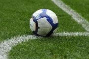 A soccer ball is rests on the pitch.