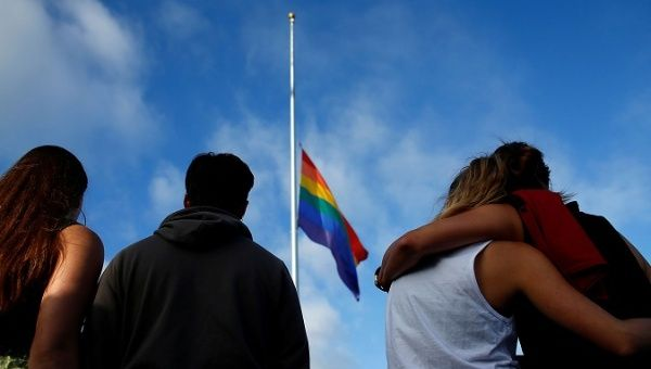 FEELING BESIEGED: Mourners in San Diego, California, gather under an LGBT pride flag at a candlelight vigil in remembrance of victims of the mass shooting in Orlando, Florida.