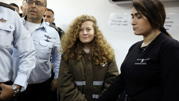 Palestinian teen Ahed Tamimi enters a military courtroom escorted by Israeli security personnel at Ofer Prison, near the West Bank city of Ramallah.