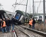 Rescue workers and police officers stand near derailed trains in Pioltello, on the outskirts of Milan, Italy, Jan. 25, 2018.