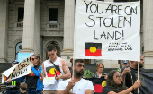 Aboriginal protesters hold signs as they demonstrate outside the Victorian State Parliament on Australia Day in Melbourne, Australia, January 26, 2017.