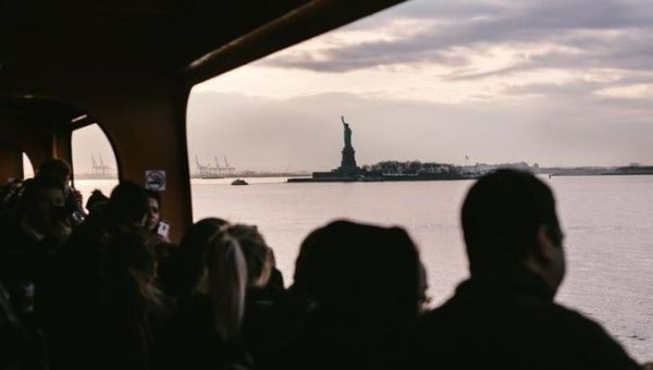 The Statue of Liberty can be seen through the windows of the Staten Island Ferry in New York, New York.