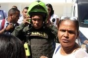 A Colombian policeman and family members transport wounded officers to a hospital after a bomb explosion at a police station in Barranquilla, Colombia.