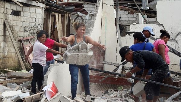 People remove debris from their damaged houses next to the scene of a bomb explosion at a police station in San Lorenzo, Ecuador.