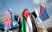 Palestinian demonstrator holds Israeli, British and U.S. flags before burning them during a protest against a U.S. decision to cut aid, in Gaza City