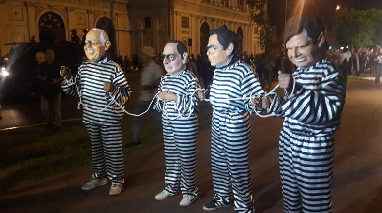 Durante la manifestación, ciudadanos usaron máscaras que representaban a autoridades peruanas mientras usaban uniformes de reos. Uno de ellos fue el jefe de Estado peruano.