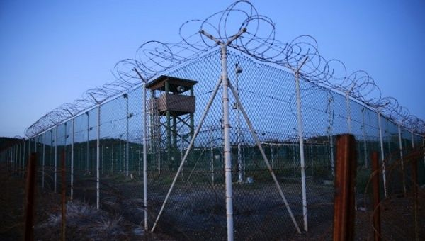 Chain link fence and concertina wire surrounds a deserted guard tower within Guantanamo