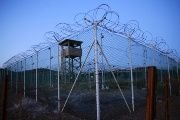 Chain link fence and concertina wire surrounds a deserted guard tower within Guantanamo's Camp Delta at the U.S. Naval Base in Guantanamo Bay, Cuba.
