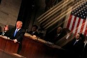 U.S. President Donald Trump and Vice President Mike Pence (C) are seen behind the reflection of a House chamber railing as Trump delivers his State of the Union address to a joint session of the U.S. Congress on Capitol Hill in Washington, U.S. January 30, 2018.