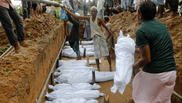 Rohingya refugees, who died after their boat capsized as they were fleeing from Myanmar, are buried in a mass grave just behind Inani beach near Cox