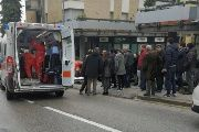 People look at healthcare personnel taking care of an injured person after being shot by gunfire from a vehicle, in Macerata, Italy, February 3, 2018.