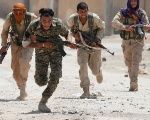 Kurdish fighters from the People's Protection Units, YPG, run across a street in Raqqa, Syria July 3, 2017.