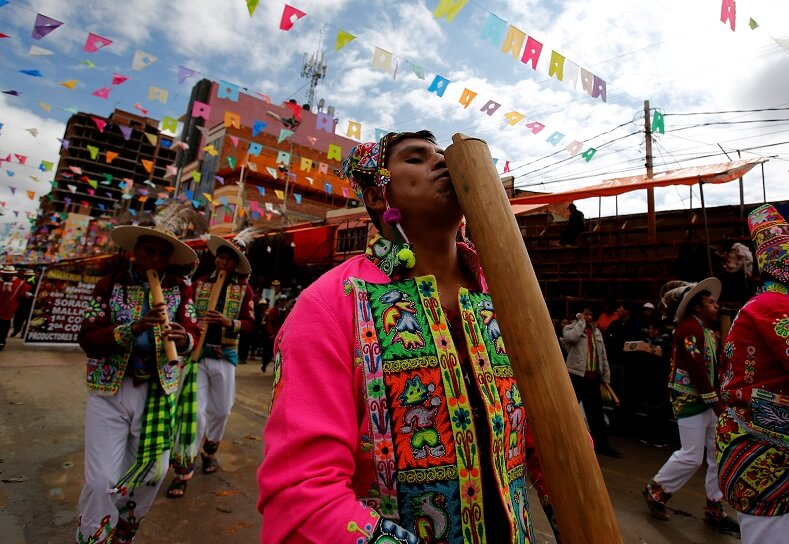 Bolivians play indigenous instruments like the Tokoro. The celebration is an expression of liberty and decolonization.