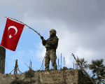 A Turkish soldier waves a flag on Mount Barsaya, northeast of Afrin.