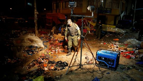 A police office inspects the site of a cooking gas bottle explosion, resulting in deaths, according to local media, during the Carnival parade in Oruro, Bolivia Feb. 10, 2018.