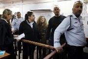 Palestinian teen Ahed Tamimi enters a military courtroom escorted by Israeli security personnel as her lawyer Gaby Lasky (L) stands near, at Ofer Prison, near the West Bank city of Ramallah, Feb. 13, 2018.