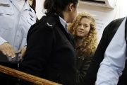 Palestinian teen Ahed Tamimi enters a military courtroom escorted by Israeli police at Ofer Prison, near the West Bank city of Ramallah, Feb. 13, 2018.
