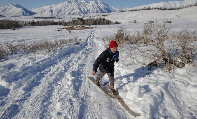 A young boy makes his way on horse-hide skis.