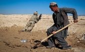 An Afghan boy works at a construction site behind a US Army soldier in Logar province, Afghanistan.