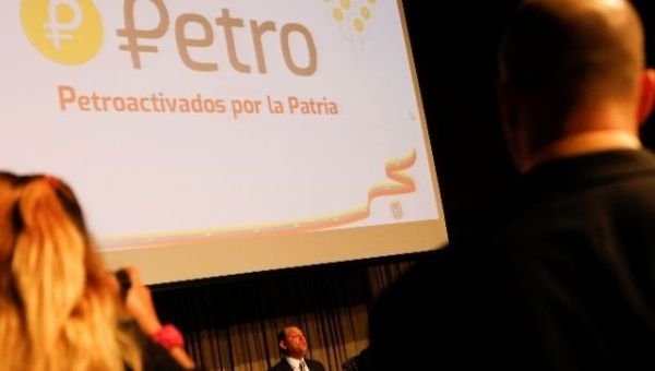 The new Venezuelan cryptocurrency the Petro logo is seen as Minister for University Education, Science and Technology Hugbel Roa talks to the media.