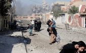 Civilians run in panic after coalition aerial bombardment hit ISIL positions in Mosul, Iraq.