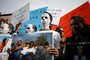 African migrants painted in white hold signs during a protest against the Israeli government's plan to deport part of their community, in front of the Rwandan embassy in Herzliya, Israel.