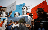 African migrants painted in white hold signs during a protest against the Israeli government