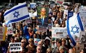 Protesters hold signs calling upon Israeli Prime Minister Benjamin Netanyahu to step down during a rally in Tel Aviv, Israel.