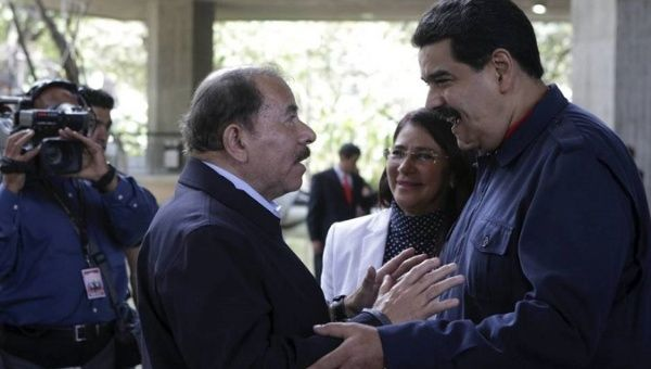Nicaraguan President Ortega (L) speaks with Venezuelan President Maduro (R).