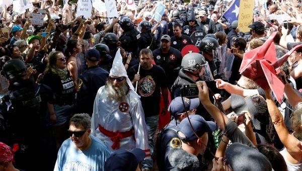 La policía antidisturbios protege a los miembros del Ku Klux Klan de los contramanifestantes cuando llegan al mitin en Charlottesville, Virginia, EE. UU., El 8 de julio de 2017.