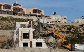 An Israeli machinery demolishes an under-construction Palestinian residential building near Hebron, in the occupied West Bank February 14, 2018.