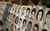 A group of people hold a banner with photographs of missing people in Guatemala.