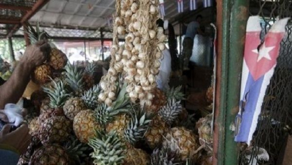 A Cuban flag hangs near pineapples and onions at a state market in Havana.