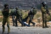 Israeli soldiers detain wounded Palestinian protesters during the clashes near Ramallah.