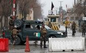 Afghan security forces keep watch at a check point near the site of a suicide attack in Kabul, Afghanistan Feb. 24, 2018.