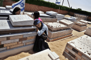Israelis mourn next to graves of relatives in a cemetery, before the exhumation of graves as part of Israel's disengagement from Gaza in 2005.