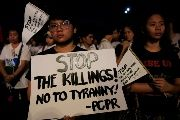 Protesters display placards in a protest against reintroducing death penalty and the drug war during