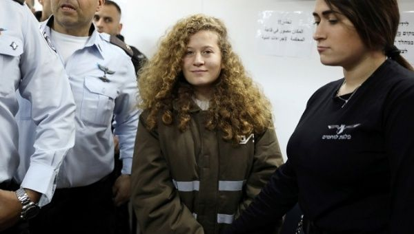 Palestinian teen Ahed Tamimi enters a military courtroom escorted by Israeli police at a prison near the West Bank city of Ramallah, Jan. 15, 2018.