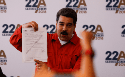 President Nicolas Maduro holds a document as he registers his candidacy for re-election at the National Electoral Council (CNE) headquarters in Caracas, Venezuela February 27, 2018.