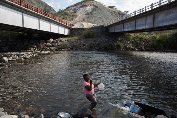 A woman washes her clothes in the Chota River just below the Panamerican highway. Poverty and lack of government investment make the Valley one of the poorest areas of Ecuador.