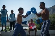 A boxing trainer in El Valle del Chota works with a youth to improve the boy's hook while other boxers in training look on.