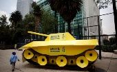 A child walks around a fake tank parked outside the US embassy during a protest held by Amnesty International in Mexico City..