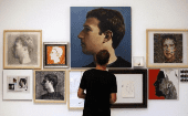 A visitor looks at portraits of Facebook