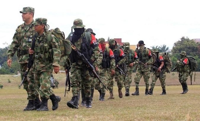 Defected members of Colombian guerrilla group ELN walk to a military base to surrender and handover their weapons, in Cali on July 16, 2013.