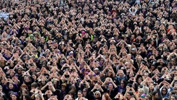 Protesters form triangles with their hands during a demonstration for women
