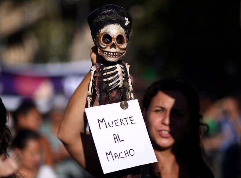 "In Argentina hundreds of thousands showed support for a bill to legalize abortions up to 14 weeks. A woman holds a puppet with a sign: ""Death to the Macho."""