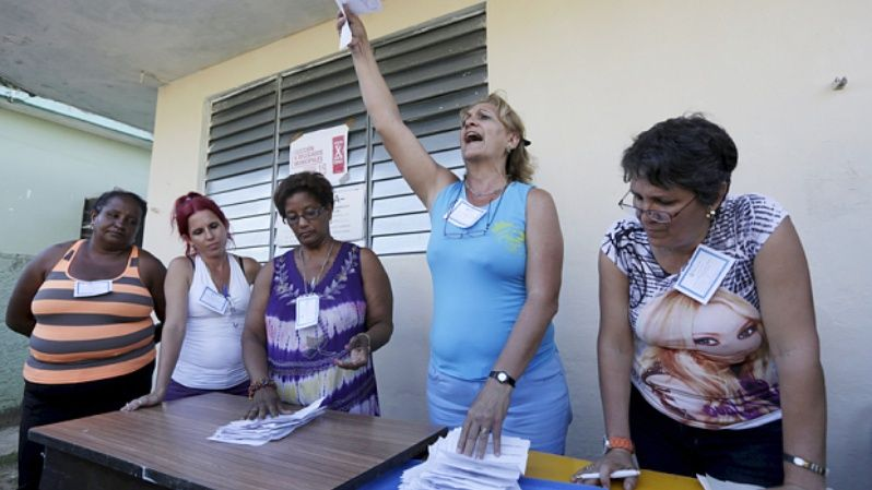 An election official counts votes on a street in Havana.