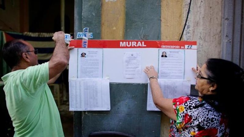 Election officials hang pictures and CVs of municipal assembly candidates moments before opening a polling station in Havana, Cuba November 26, 2017.
