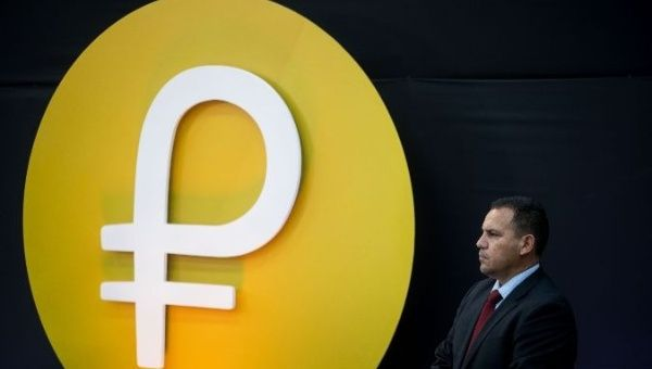 A Venezuelan security official stands in front of the Petro cryptocurrency logo.