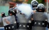 A police officer fires tear gas during clashes with demonstrators as Honduran President Juan Orlando Hernandez is sworn in for a new term in Tegucigalpa